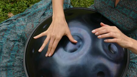 Beautiful female hands on a perfect musical percussion instrument. Sound Meditation