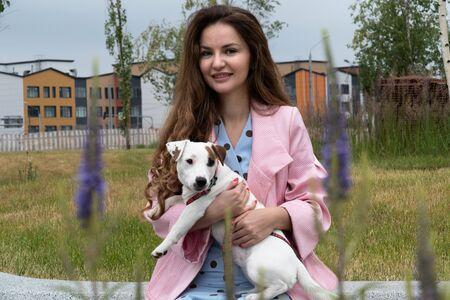 Der Hund sitzt in den Armen einer Frau im Park.