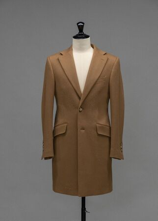 Beige coat on a mannequin in the studio on gray background