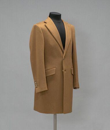 Beige coat on a mannequin in the studio on gray background Standard-Bild