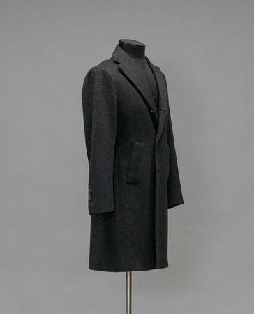 Black coat on a mannequin in the studio on gray background Standard-Bild
