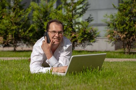 Freelancer at work with laptop and mobile phone sitting on the green grass Imagens