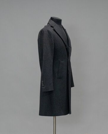 Black coat on a mannequin in the studio on gray background