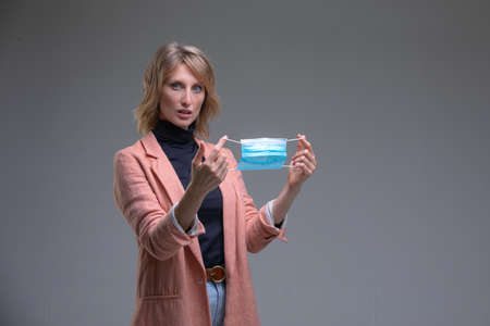 Head portrait attractive blond woman hold her surgical mask protecting from COVID19 or corona virus. Personal care during pandemic infectious. End of pandemia concept. Stock fotó