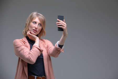 Portrait of cool cheerful woman having video-call with lover holding smart phone in hand shooting selfie on front camera isolated on grey background enjoying weekend vacation Stock fotó