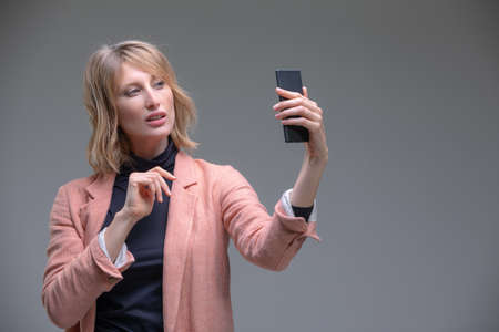 Portrait of cool cheerful woman shooting selfie on front camera isolated on gray background enjoying weekend vacation Stock fotó