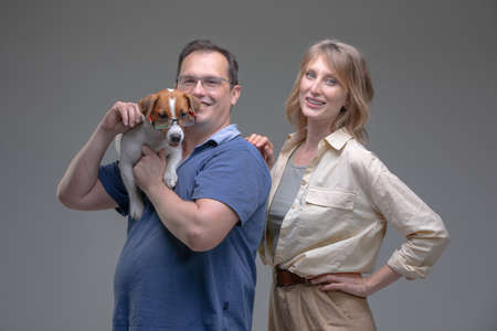 Happy woman and man in studio plays with jack russell terrier dog. Pet love concept.