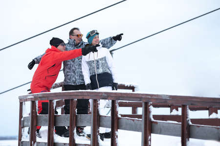 Skiers share their impressions against the background of the ski lift