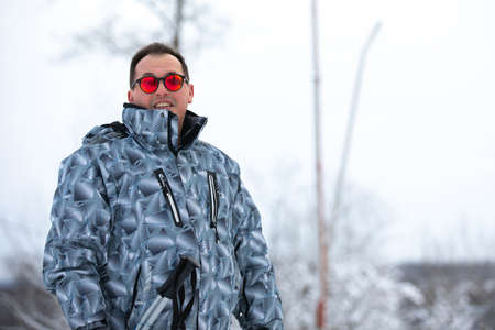 Man in red glasses and sport wear stands alone against white outdoors. Noname wear with abstract pattern. 版權商用圖片
