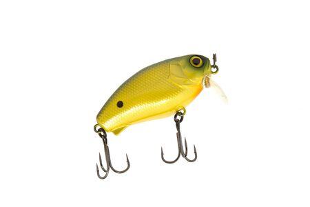approximate: Yellow lure with sharp hooks in the approximate form.