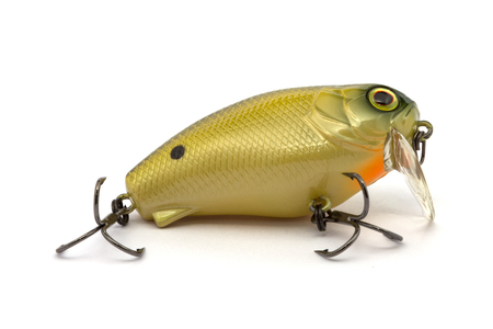 Yellow lure with sharp hooks in the approximate form.