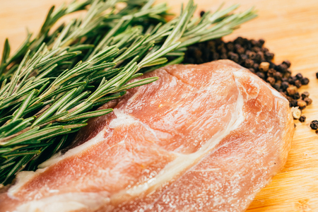 raw meat, sprig of rosemary and pepper on a wooden light background.
