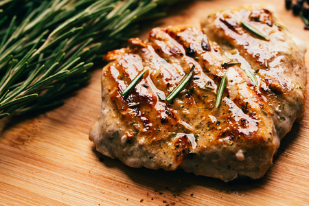 sprig: grilled meat, sprig of rosemary on a wooden light background.