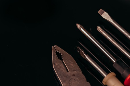 many different screwdrivers and pliers on a dark background bunch.