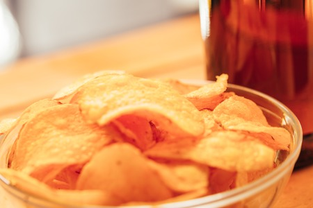 bowl of chips with brown beer bottle on blurred background.