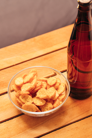 rusk: rusk bowl with brown beer bottle on a wooden background.