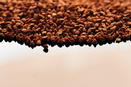 caloric: many buckwheat scattered on a black background.