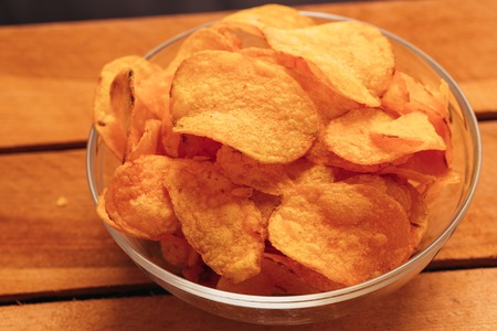 clear bowl of potato chips on a wooden background.