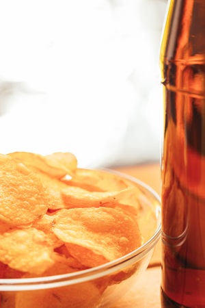 condensacion: bowl of chips with brown beer bottle on blurred background.
