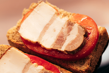 sandwich with bacon and tomato on dark background.