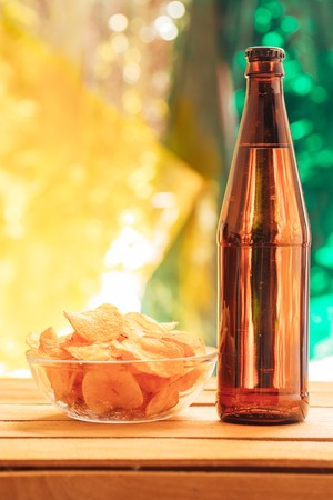 brown beer bottle with a bowl of chips on a blurred background. Stock Photo