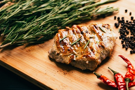 grilled meat, sprig of rosemary and red hot pepper on a wooden light background.
