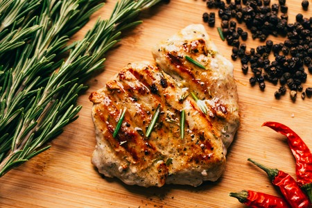 sprig: grilled meat, sprig of rosemary and red hot pepper on a wooden light background.