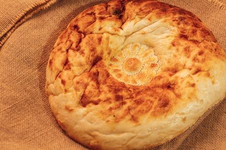 uzbek: National Uzbek bread on sackcloth, top view. Stock Photo
