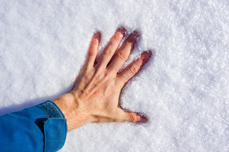 Hand touches the snow
