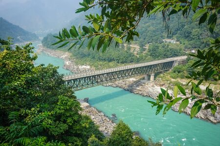 Bridge over the turquoise ganges river in rishikesh
