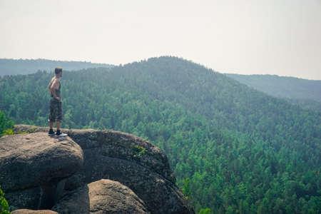 Hiker on a rock in the Krasnoyarsk Pillars nature reserve Stock Photo
