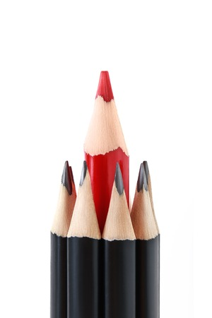 standing out from the crowd: Red pencil standing out from crowd of plenty identical black pencils on white background. Leadership, uniqueness, independence, initiative, strategy, dissent, think different, business success concept
