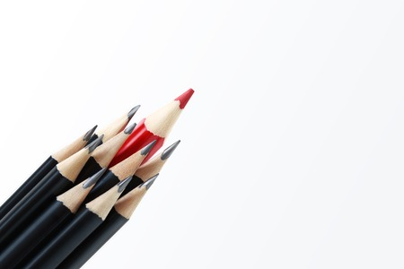 different strategy: Red pencil standing out from crowd of plenty identical black pencils on white background. Leadership, uniqueness, independence, initiative, strategy, dissent, think different, business success concept