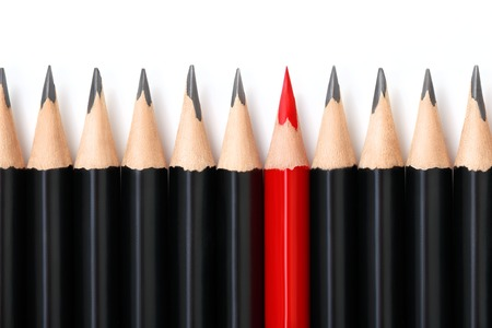 dissent: Red pencil standing out from crowd of plenty identical black pencils on white background. Leadership, uniqueness, independence, initiative, strategy, dissent, think different, business success concept