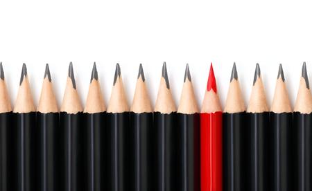 Lápis vermelho, destacando-se da multidão de muitos lápis pretos idênticos em fundo branco. Liderança, exclusividade, independência, iniciativa, estratégia, dissidência, pense diferente, conceito de sucesso nos negócios Foto de archivo