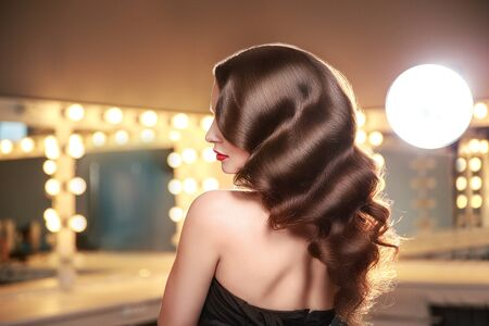 Long curly hair. Back, side view. Brunette in makeup room with studio lights. Portrait.