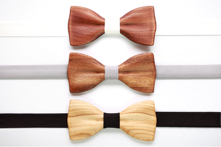 dissent: Three wooden bow ties with white, grey and black ribbons. Flat lay, isolated. Team work, career, hipster, wedding concept. White stripe, black stripe. Stock Photo