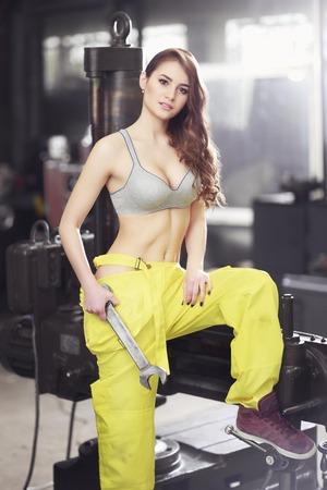 Leuke sexy vrouw monteur holdingsmoersleutel. Meisje weared in geel werk overalls en grijze uplift verhinderde dat de fabriek
