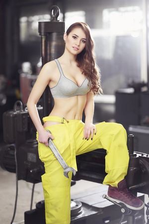 Nice woman mechanic holding wrench. Girl weared in yellow work overalls and grey uplift standing over the factory