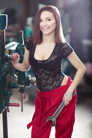 Nice sexy woman mechanic-engineer holding wrench. Girl weared in red work overalls standing over the factory Standard-Bild