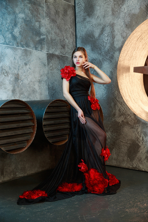 young girl in black vintage dress posing near ventilation pipes. proudly and thoughtfully looks aside. Фото со стока
