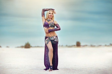 Beautidul smiling lady dancing Belly dance in the sands desert. Stock Photo