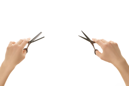 Two hand holding different hair scissors isolated on white background.