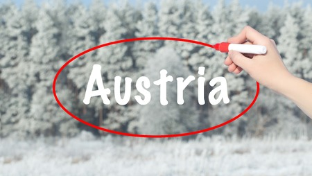 Woman Hand Writing Austria with a marker over transparent board. Isolated on winter forest. Life, technology, internet concept