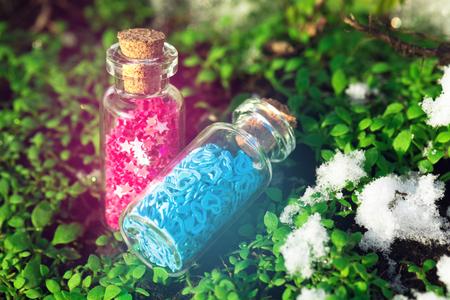estrellas moradas: Dos botellas de cristal con las estrellas púrpuras y corazones azules en el bosque Foto de archivo