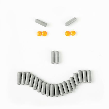Angry smile made from many pills and capsules. wellness concept.