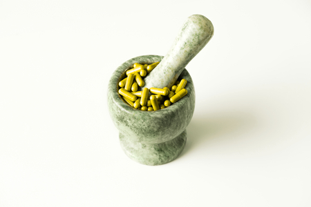 sobredosis: Yellow capsules and orange pills with mortar and pestles on white background Foto de archivo