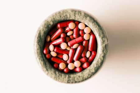 Red capsules and orange pills with mortar and pestles on white background