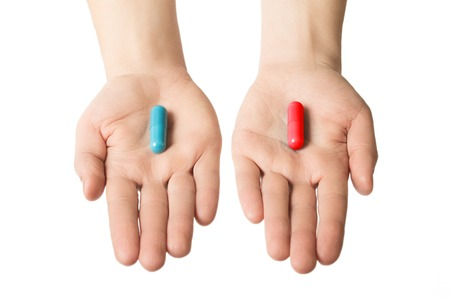 Man hands giving two big pills. Blue and red. Make your selection. Health or ill. Choose your side.
