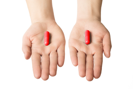Man hands giving two big red pills. Make your choice consept. excitation and adrenalin.